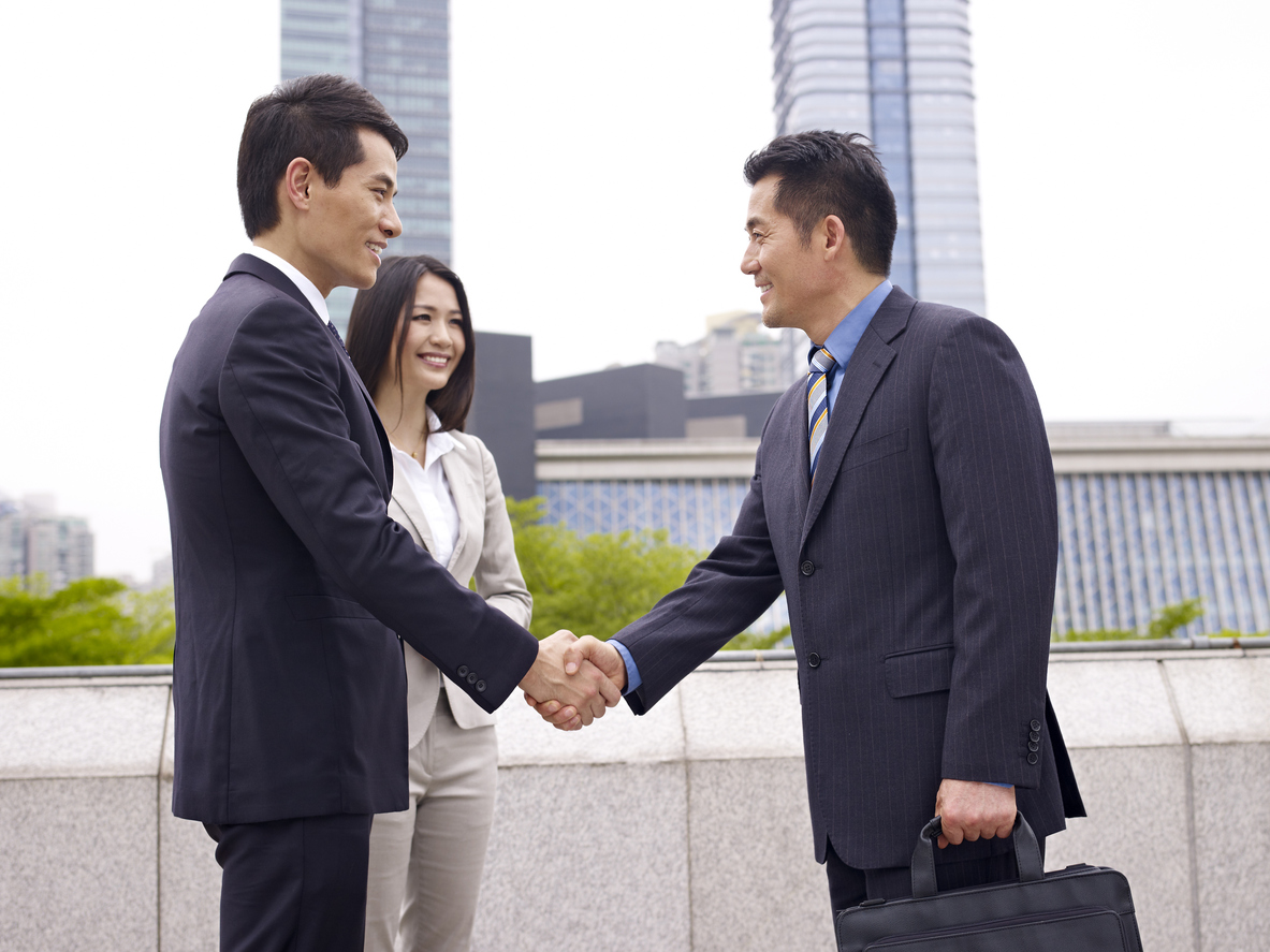 business people shaking hands and smiling.